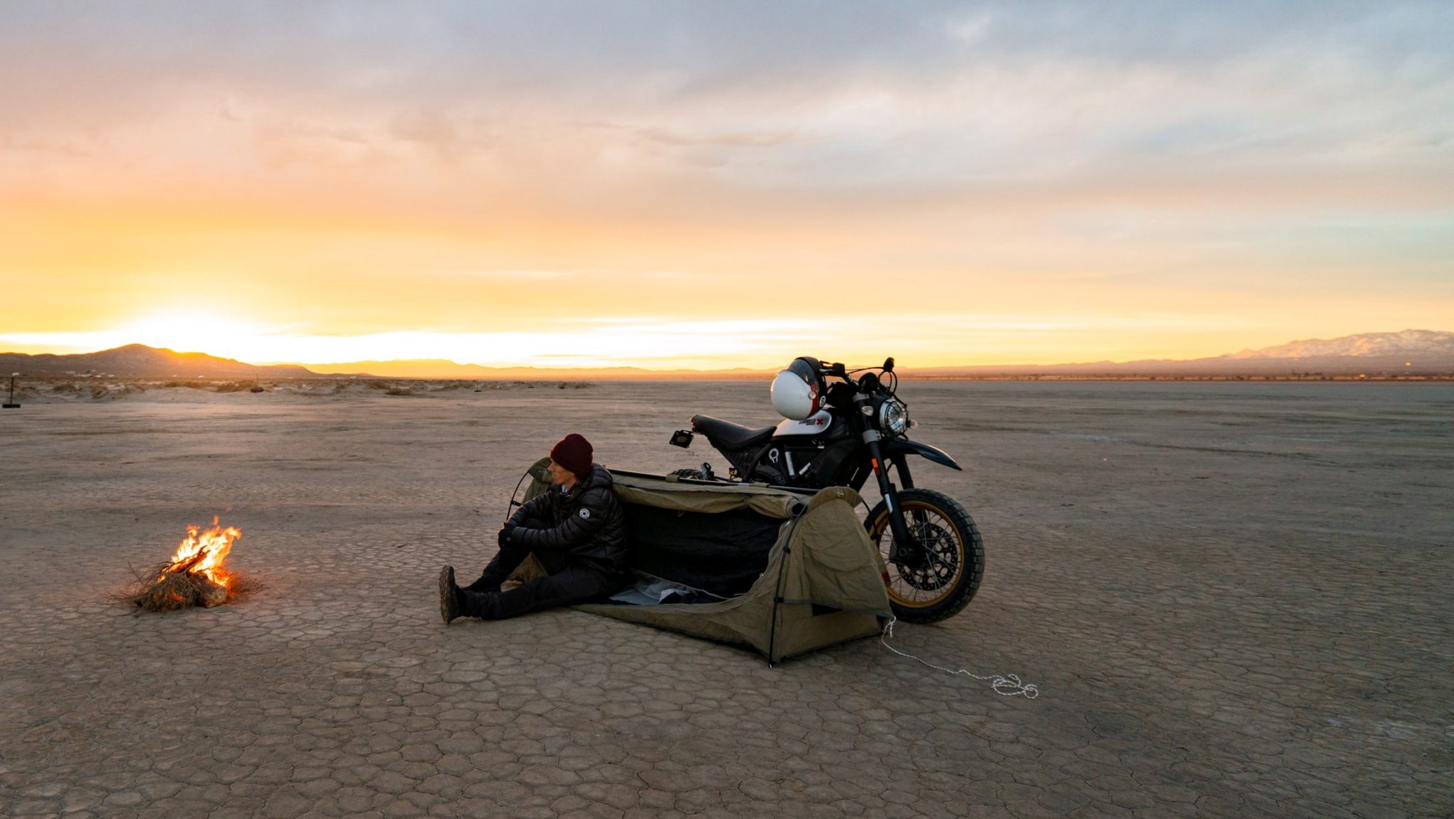 Man on a motorcycle camping trip with fire burning and sunset in the distance