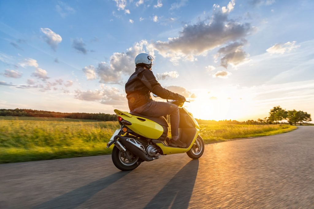 Person riding their motorcycle towards the sun with a beautiful landscape in the background