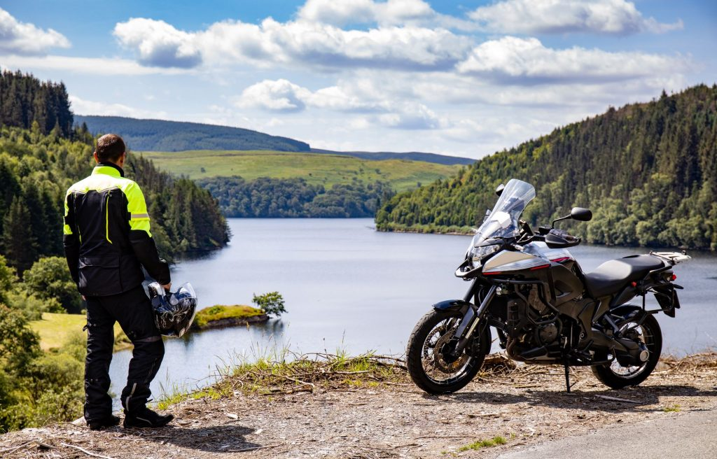 Man touring Wales in the UK wearing reflective gear looking at beautiful scenery
