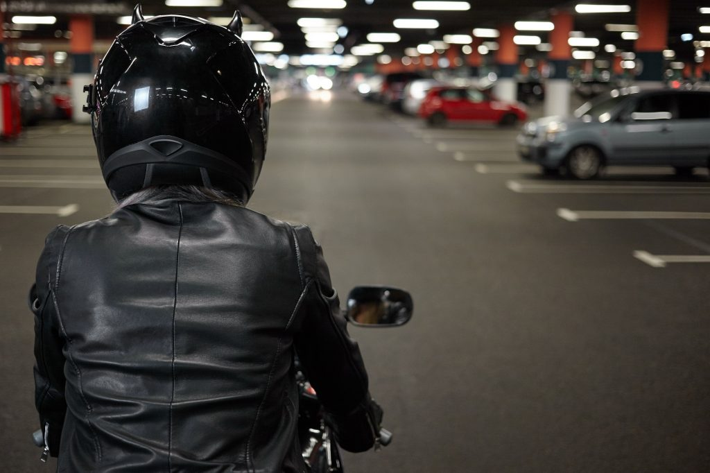 Person on their motorcycle in a basement parking complex