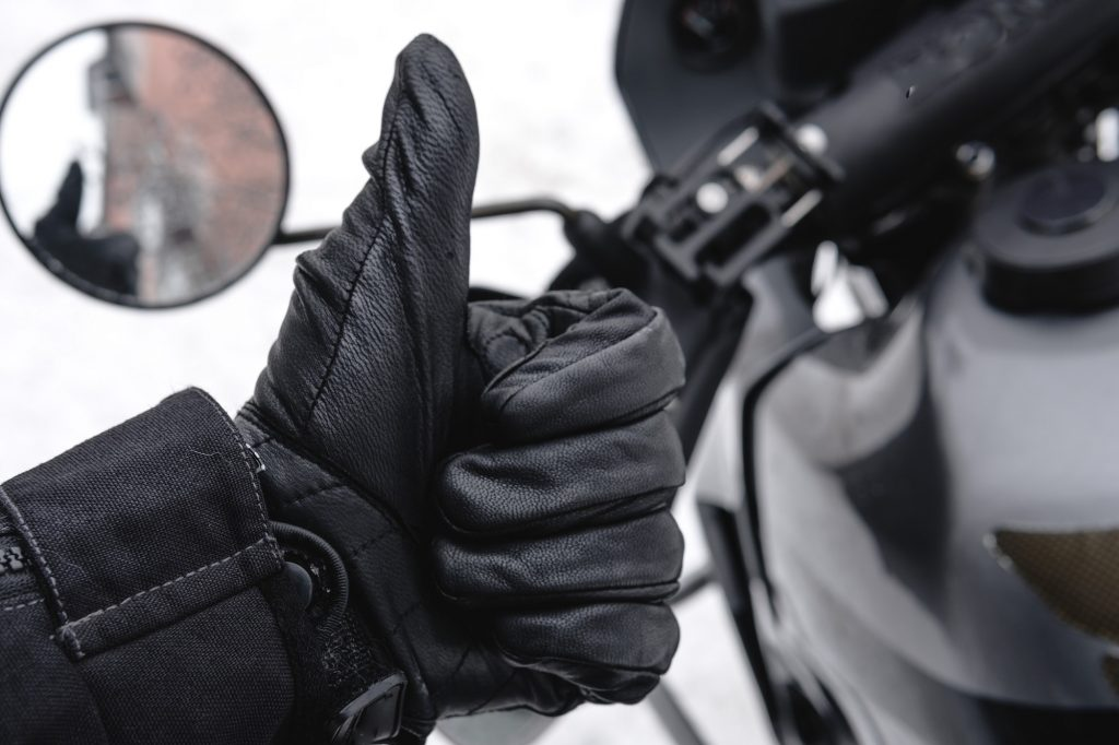 Close up of person giving a thumbs up in a leather glove with their bike in the background and snow on the ground