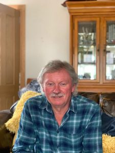 Dave McCourt smiles for the camera at home