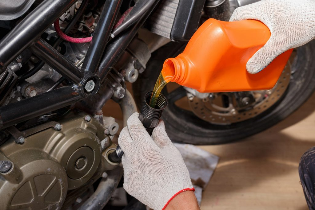Person topping motorcycle oil up