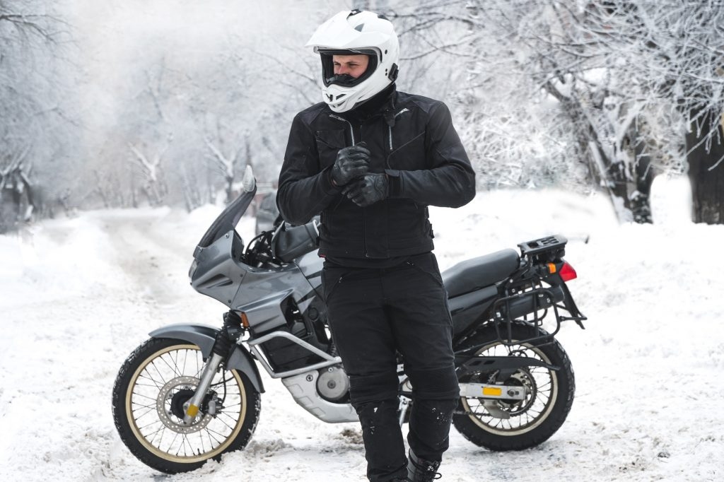 Man walking in the snow with motorcycle in the background