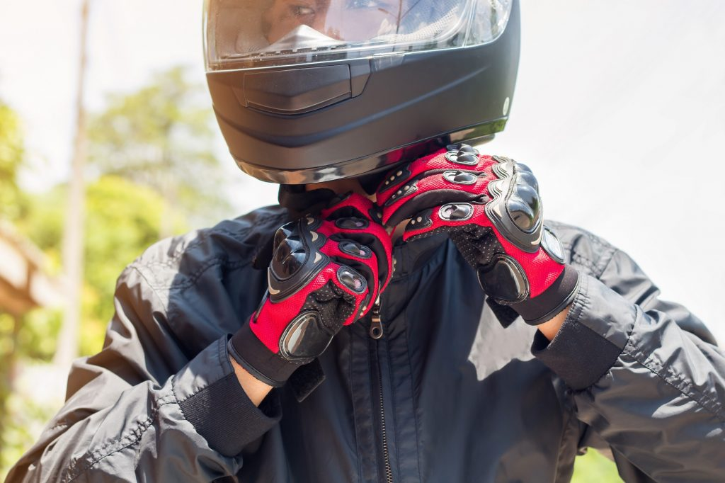 Man putting his helmet on, already kitted out with motorcycle gear