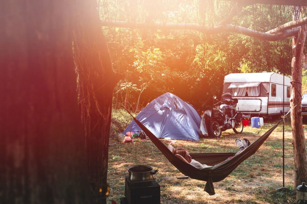 Person lounging on hamock with motorcycle, tent and trailer in the background