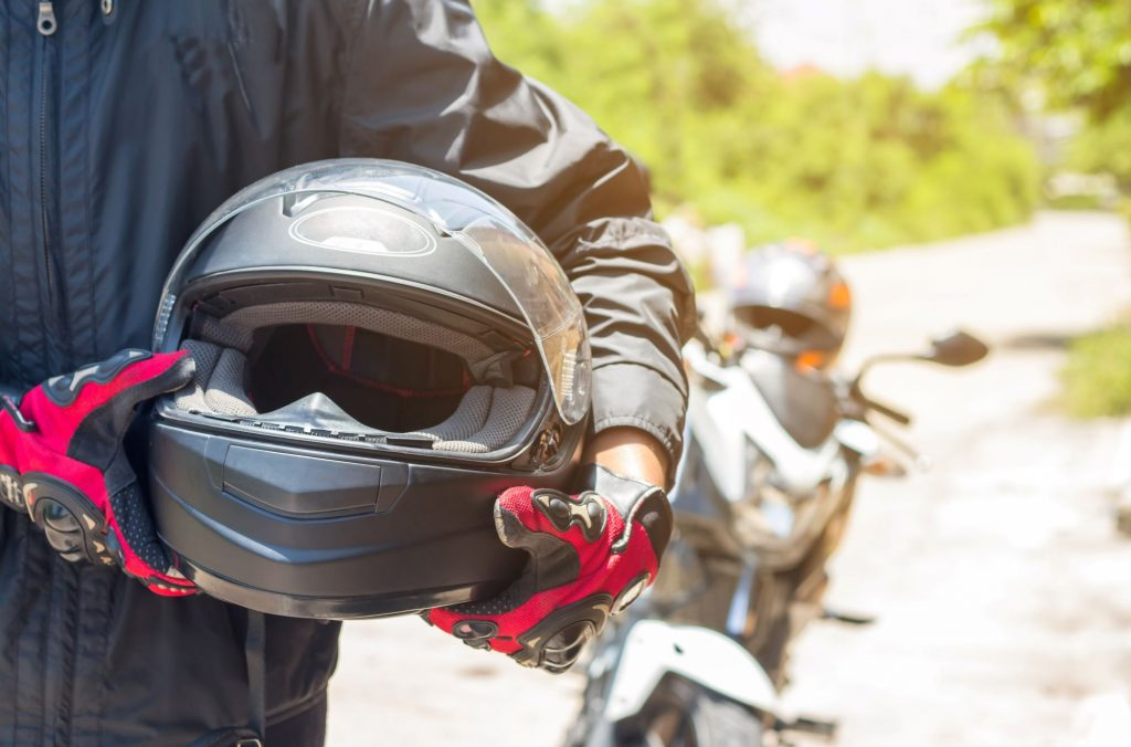Person holding their motorcycle helmet with gloves on