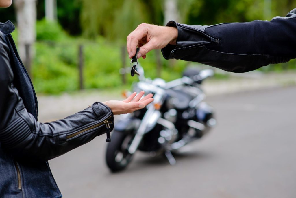 Two people exchanging keys with motorcycle in the background