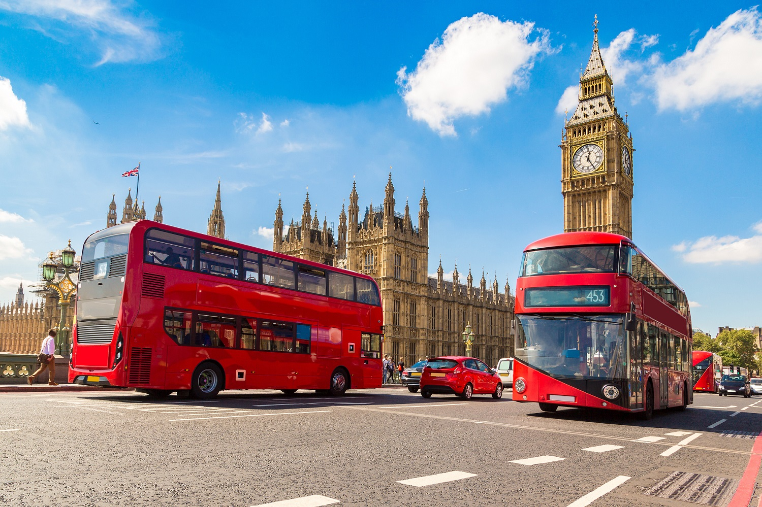London road with Big Ben and Westminster Bridge in the background and red double decker buses and cars in the foreground
