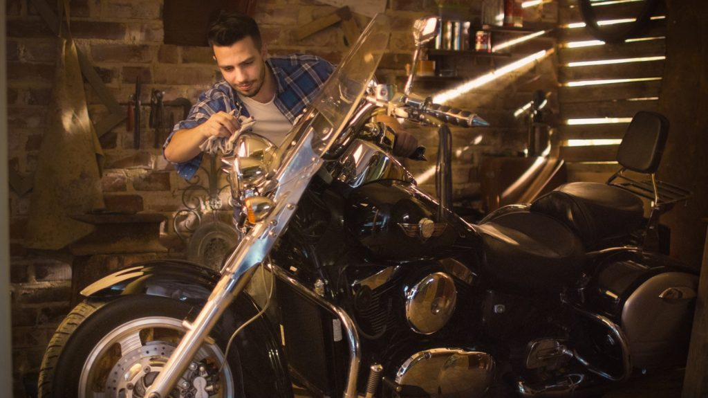 Man is cleaning and polishing chrome motorcycle in a garage