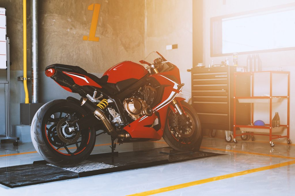 Closeup of sport motorcycle in repair station and body shop with soft-focus and over light in the background